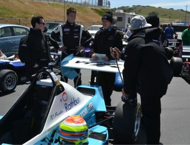 Post race talk at the famed Mazda Raceway Laguna Seca in Monterey, CA.  Jeff Andretti (Coach) in glasses.  Eric Purcell- Engineer in Duck Hat, JJ Ho, mechanic, with foot on tire
