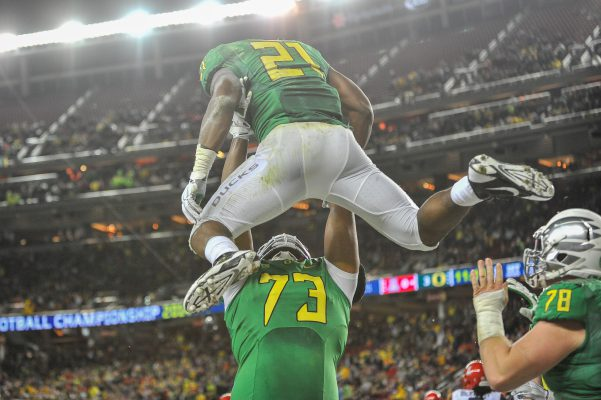 Crosby hoisting star running back Royce Freeman into the air after a touchdown in the Pac-12 championship game.